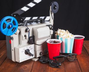 A late-20th-century movie projector on a hardwood floor, with sunglasses, two soft drinks, and a bucket of popcorn - image via freepik
