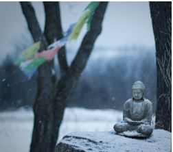 A tiny Buddha statue on a rock, with prayer flags in the background, on a snowy day